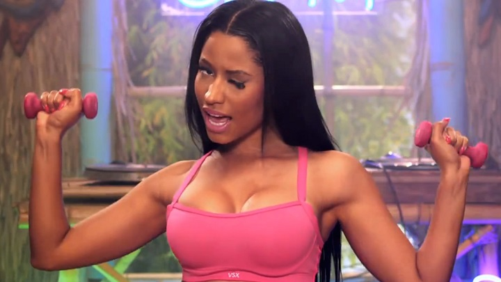 Nicki Minaj holds weights, winking seductively, in Anaconda.