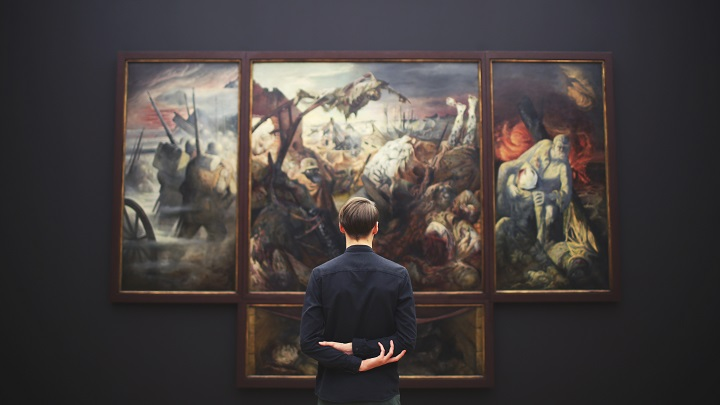 A man stands in an art gallery, forming his own personal interpretation.